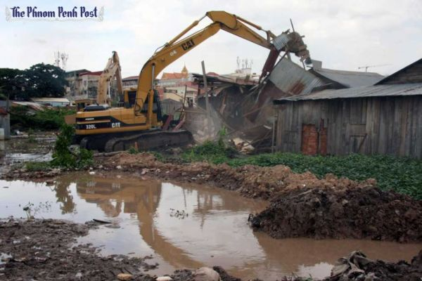 Buildings are demolished by excavators during forced evictions in Phnom Penh at the Boeung Kak lake community in 2010. (Photo from the Phnom Penh Post)
