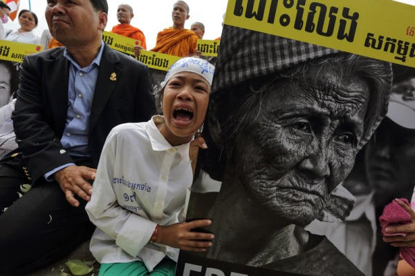 Dar Rachana, 12, protests outside Phnom Penh's Prey Sar prison on Sunday while holding a poster of her grandmother, Nget Khun, who, along with six fellow activists from the Boeung Kak community, was sentenced to a year in prison on November 11. (Photo from the Cambodia Daily)