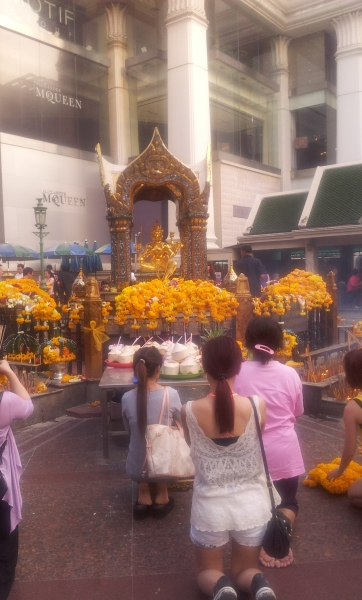 The different faces of Bangkok: designer shop Alexander McQueen stands behind worshippers at the Erawan shrine in central Bangkok